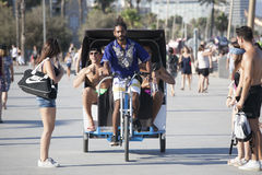 Young rickshaw gives a lift to cheerful tourists along the beach in Barcelona, Spain Stock Photography