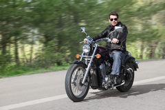 Young Rider Driving Motorcycle. Young rider driving his cruiser-type motorcycle on the country road Royalty Free Stock Photo