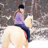 Young rider girl on albino horse in winter forest Stock Images