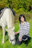 Young rider girl with her white horse Royalty Free Stock Photo