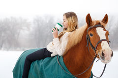 Young rider girl relaxing on horseback with coffee. Young rider girl relaxing on horseback with cup of coffee Royalty Free Stock Photo