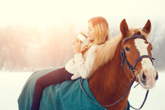 Young rider girl relaxing on horseback with coffee. Young rider girl relaxing on horseback with cup of coffee in sunset beams Stock Image