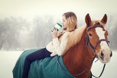 Young rider girl relaxing on horseback with coffee. Young rider girl relaxing on horseback with cup of coffee in winter park Stock Image