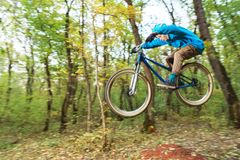 A young guy in a helmet flies landed on a bicycle after jumping from a kicker. A young rider in a helmet and a blue sweatshirt flies on a bicycle after jumping Royalty Free Stock Photography