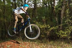 A young guy in a helmet flies on a bicycle after jumping from a kicker Stock Image