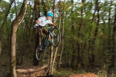 A young guy in a helmet flies on a bicycle after jumping from a kicker Royalty Free Stock Photos