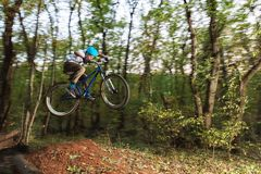 A young guy in a helmet flies on a bicycle after jumping from a kicker Royalty Free Stock Image