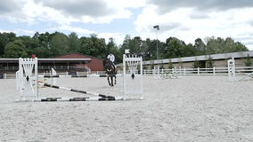 Young rider jump over the barrier at the arena stock video footage