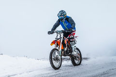 Young rider on motorcycle driving on snowy highway Stock Photo