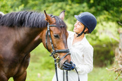 Young rider woman in helmet holding bay horse Stock Image