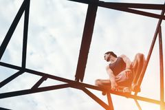 Young risky guy balancing and sitting on high metal construction. Outdoors Stock Image