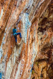 Young Rock Climber ascending steep colorful rocky Wall Lead Climbing Stock Photos