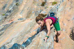 Young Rock Climber ascending steep colorful rocky Wall Lead Climbing. Young cute Female Climber makes difficult Move leading multi pitch route on colorful orange Stock Photos
