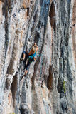 Young Rock Climber ascending steep colorful rocky Wall Lead Climbing Royalty Free Stock Image