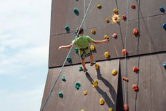 A young rock climber descends from an artificial mountain with safety cords and ropes in a sports amusement park stock photo