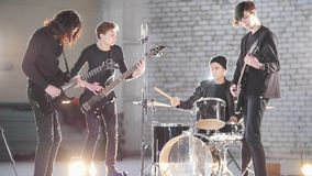 A young rock group having a repetition in a garage. Members of a group wearing black clothes. Bright lighting. Mid shot stock photo