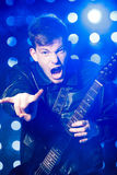 Young rock musician playing electric guitar and and making rock gesture. Rock star on background of spotlights Stock Photography