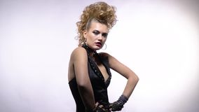 Young rocker lady with crazy hairstyle arching her back while posing, slow motion. Blonde girl wearing rocker clothes, makeup and amazing hairstyle, posing and stock footage