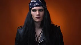 Blank stare of a rocker man wearing bandana and leather jacket, close up. Young rocker with long black hair, with bandana on his head, looking at the camera stock footage