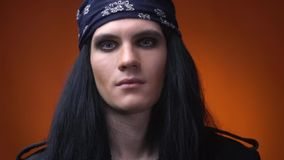 Young rocker with makeup, long hair and bandana on his head, close up. Handsome man with blue eyes and makeup, wearing bandana and leather jacket, smiling stock footage