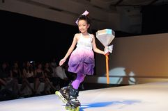 Young roller girl on fashion show. Young model on catwalk with skating stock photography