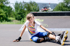 Young rollerblader taking a rest. Young attractive teenage female rollerblader taking  rest from skating sitting  asphalt at the skate park  hot summer sun Stock Image