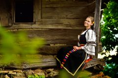 Young Romanian girl smiling on the porch of an old house. In the summer time royalty free stock image