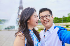 Young romantic Asian couple in Paris. Young romantic Asian couple of tourists on vacation taking selfie in front of Eiffel Tower, Paris, France Royalty Free Stock Photography
