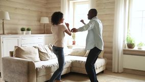 Young romantic black couple dancing in modern living room