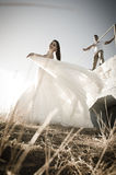 Young romantic bridal couple outdoors flirting in long grass Royalty Free Stock Photo