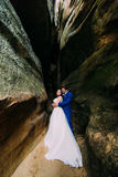 Young and romantic bride with her loving groom posing in dark weathered rock cleft Stock Images