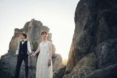 Beautiful wedding couple bride and groom at wedding day outdoors. Young and romantic bride with her loving groom posing in darkened sandstone cleft Stock Photos