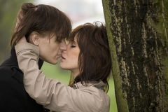 Young romantic couple. Kissing near tree Stock Images