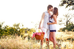 Young romantic couple. Kissing on their way to a picnic Royalty Free Stock Photos