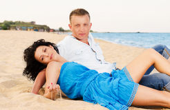 Young romantic couple on the beach. Young attractive romantic couple lying back and relaxing close together on a sandy beach in summer sunshine Royalty Free Stock Images