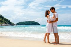 Young romantic couple on a beach, copy space left Stock Photos