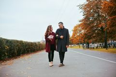 Young romantic couple, beautiful girl with flowers has dating in the park. Man in gray overcoat and model in red coat. love royalty free stock photography