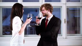 Young romantic couple celebrating with glasses of red wine. Romantic Couple drinking red wine. Beautiful young couple. With glasses of red wine stock footage