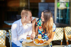 Young romantic couple in a cozy outdoor cafe in Paris, France Royalty Free Stock Images