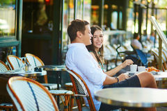 Young romantic couple in a cozy outdoor cafe in Paris, France Royalty Free Stock Photo