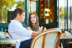 Young romantic couple drinking coffee in a cozy outdoor cafe in Paris, France Stock Image