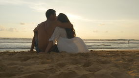 Young romantic couple is enjoying beautiful sunset sitting on the beach and hugging. A woman and a man sits together in Stock Images