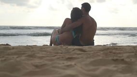 Young romantic couple is enjoying beautiful view sitting on the beach and hugging at evening. A woman and a man sits. Together in the sand on the sea shore stock video footage