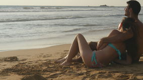 Young romantic couple is enjoying beautiful view sitting on the beach and hugging. A woman and a man sits together in Stock Photo