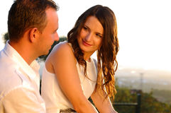 Young romantic couple eye contact at sunset. Young romantic couple in white clothing eye contact at sunset stock photography
