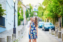 Young romantic couple hugging on Montmartre. Young romantic couple hugging and kissing tenderly on a street of Montmartre in Paris, France Stock Image
