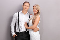 Young romantic couple hugging and posing. Against a gray wall royalty free stock images
