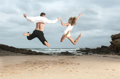 Young romantic couple jumping on the beach at sunrise Stock Photo