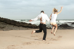Young romantic couple jumping on the beach at sunrise Royalty Free Stock Images