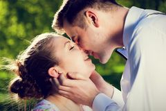 Young romantic couple kissing with love in summer park. Dating, fiance with fiancee, romance Royalty Free Stock Photography